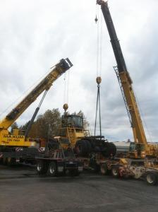 2 cranes lifting large forklift
